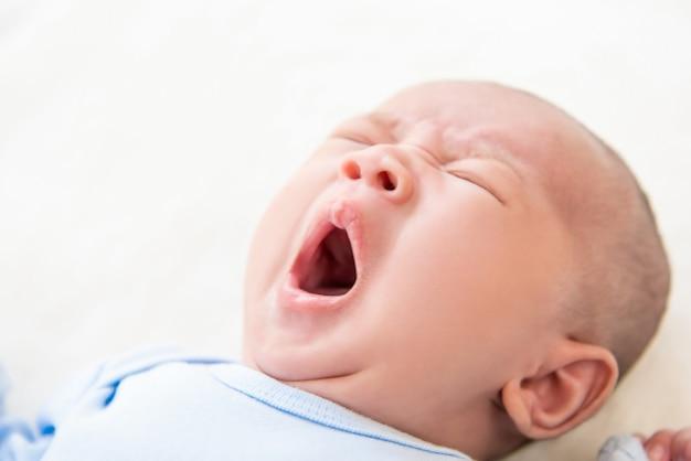 ベッドであくび眠いかわいい新生児