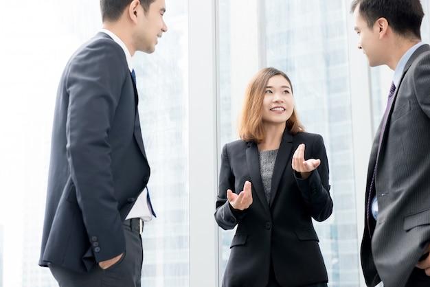 事務所ビルの廊下で彼女のチームと話しているアジアの実業家