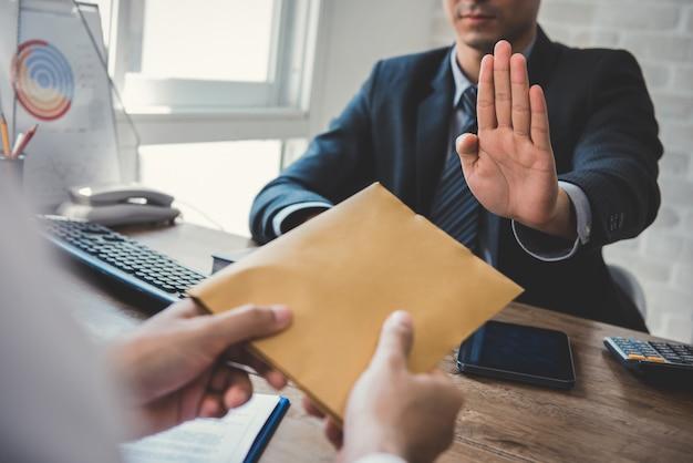 封筒にお金を拒否するビジネスマン-贈収賄防止および腐敗の概念