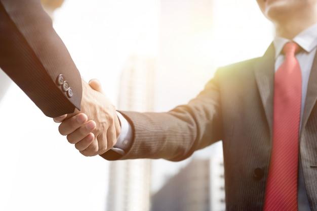 Бизнесмены делают рукопожатие - приветствие, сделки, слияния и поглощения концепции