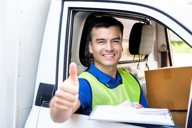 Доставка человек сидит в машине, как водитель, давая пальцы вверх