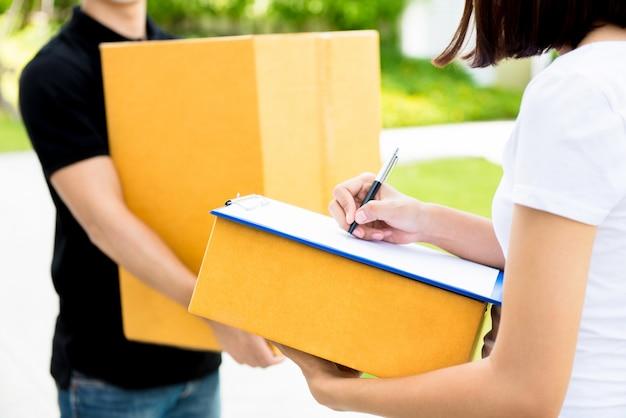 Женщина подписывает документ, получает посылку от доставщика