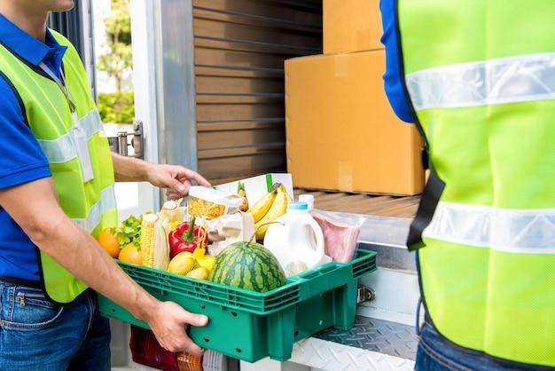 配達する車から取り出す前に食べ物をチェックする配達人