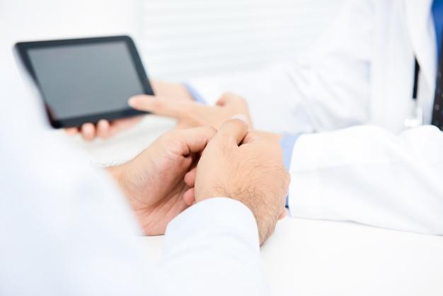 Доктор, объясняя лечение мужского пола пациента с помощью планшетного компьютера