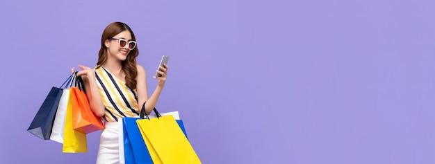 携帯電話でオンラインショッピング美しいアジアの女性