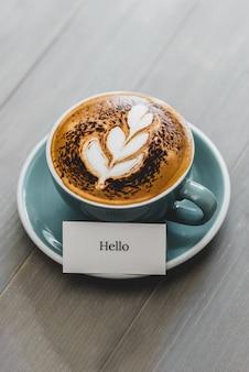 ラテアートと木製のテーブルにこんにちはあいさつ文とコーヒーのカップ
