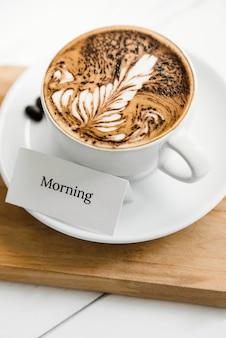 挨拶テキストの横にあるカップでシダパターンラテアートコーヒー