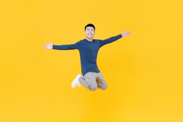 若いアジア人の笑顔と両腕でジャンプ