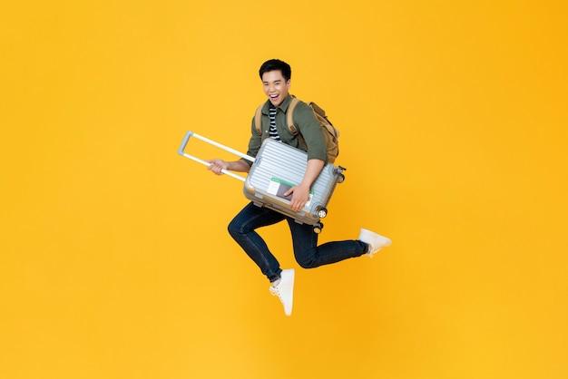 Возбужденный азиатский турист человек прыгает в воздухе готов путешествовать