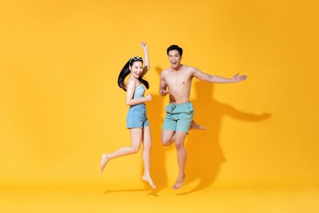 夏のビーチのカジュアルな服を着てジャンプでエネルギッシュな幸せなアジアカップル