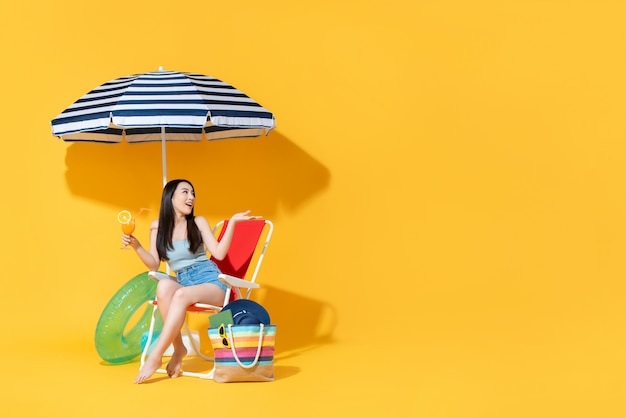 Удивленная красивая азиатская женщина сидя на шезлонге