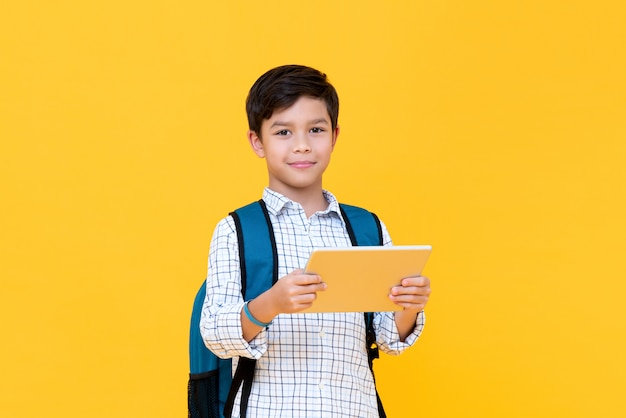 Красивый молодой мальчик в рюкзаке, держа планшет
