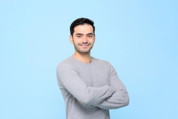 Портрет улыбающегося дружелюбного красавца в простой серой футболке со скрещенными руками, изолированные в свете