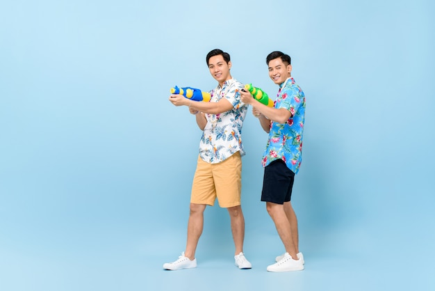 Улыбающиеся счастливые друзья мужского пола, играющие с водяными пистолетами для фестиваля сонгкран в таиланде и юго-восточной азии