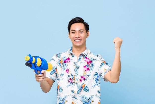 Улыбающийся красивый азиатский человек играет с водяной пушкой и поднимает кулак для фестиваля сонгкран в таиланде и юго-восточной азии