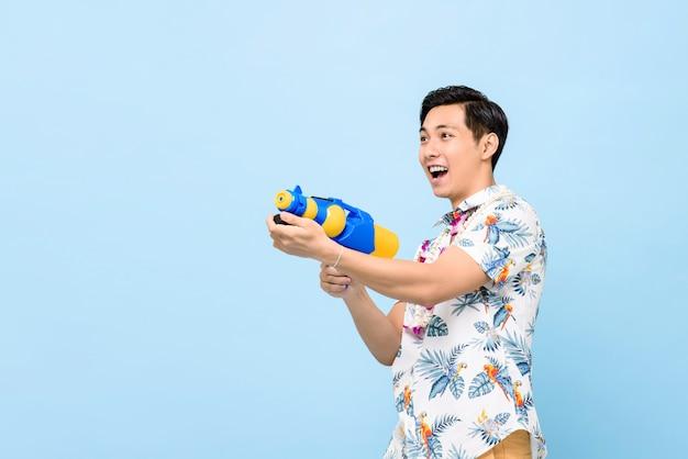 Улыбающийся красивый азиатский мужчина играет с водяной пушкой для фестиваля сонгкран в таиланде и юго-восточной азии