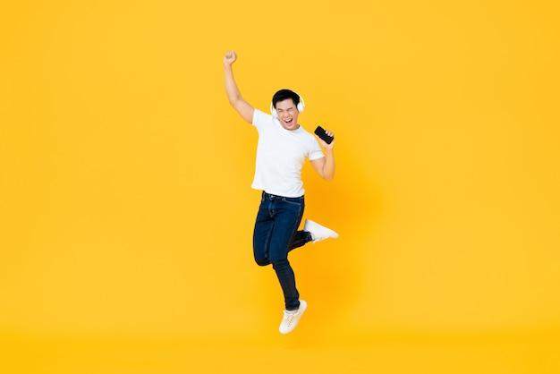 Наушники счастливого молодого азиатского человека нося слушая к музыке от мобильного телефона и скача с поднимать кулака изолированные на желтой стене
