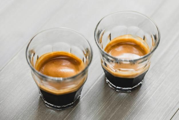 ヴィンテージの木製のテーブルにグラスでエスプレッソコーヒーをダブルショット