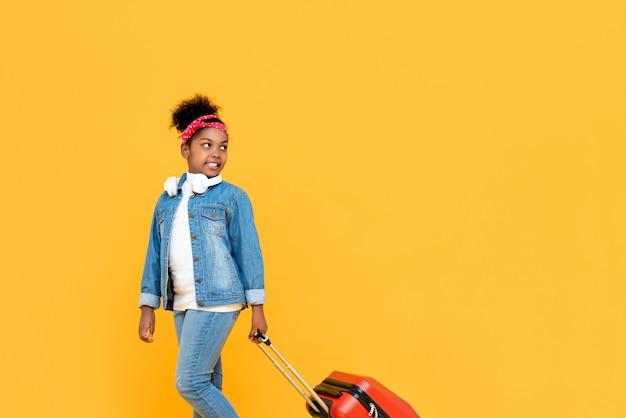 黄色の壁に分離された旅行の準備ができて荷物でファッショナブルなかわいいアフリカの女の子