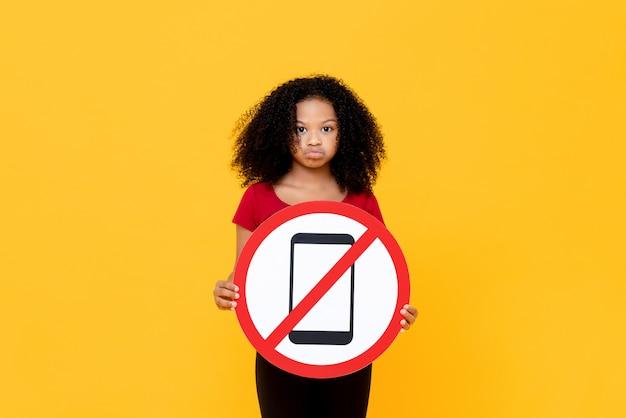 Смешанная раса африканская девушка не показывает знак использования мобильного телефона, изолированных на красочные желтой стене
