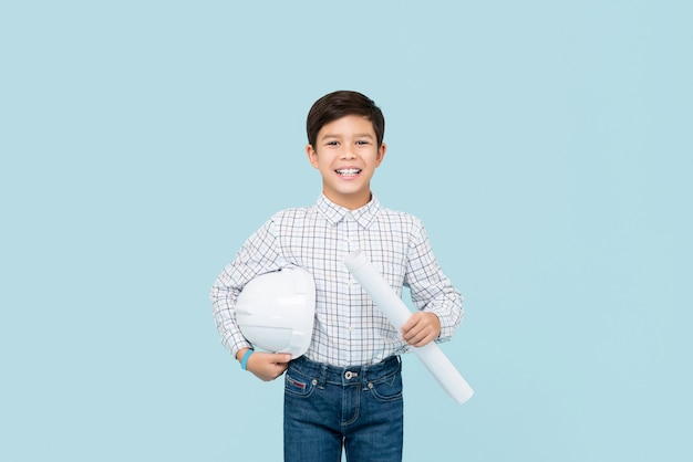 Улыбающийся молодой мальчик смешанной расы азиатских стремятся быть инженером, держа план и шлем, изолированные на светло-голубой стене
