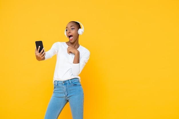 Наушники уверенно афро-американской женщины нося слушая к музыке от мобильного телефона в желтой изолированной стене