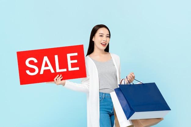 Усмехаясь хозяйственные сумки нося азиатской женщины показывая красный знак продажи