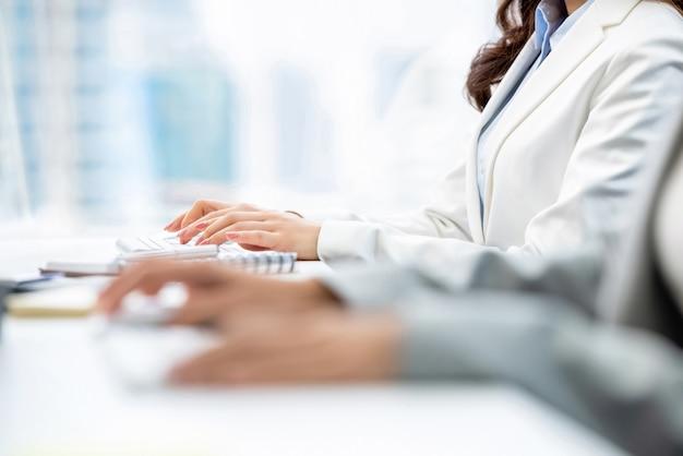 オフィスで働くコンピューターのキーボードで入力する女性のホワイトカラー労働者の手