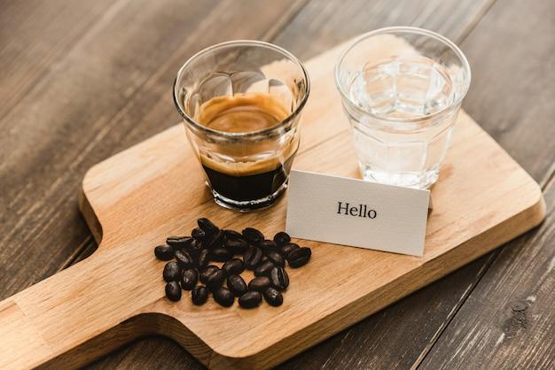 淹れたての黒エスプレッソコーヒーとショットグラスの水を木製の大皿でお召し上がりいただけます