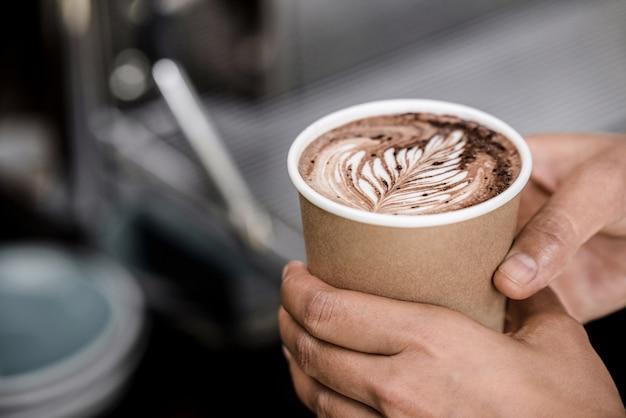 シダのラテアートデザインで淹れたてのホットコーヒーのカップを奪う男性の手のショットを閉じる