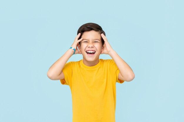 Счастливый улыбающийся азиатский мальчик с руками сжимая голову, изолированные на светло-голубой стене