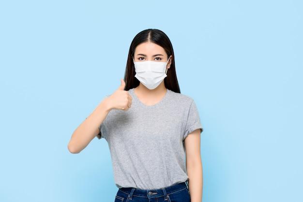 Молодая азиатская женщина, носящая маску, защищающую коронавирус и аллергию, бросающую большие пальцы, изолированную на светло-голубой стене