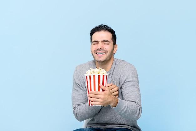 Молодой человек, держащий попкорн, смеясь во время просмотра фильма, изолированные на светло-голубой стене