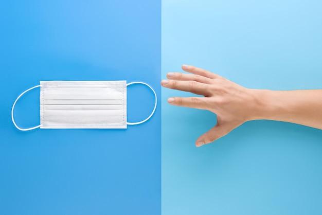 Рука протягивает руку к медицинской маске для защиты от микробов и вирусов во время пандемии, вид сверху