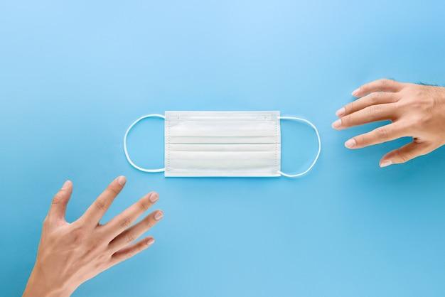 Руки протягивают руку, чтобы получить медицинскую маску для защиты от микробов и вирусов во время пандемии