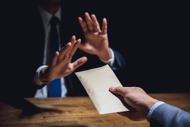Бизнесмен отвергает деньги в конверте, концепция борьбы с взяточничеством