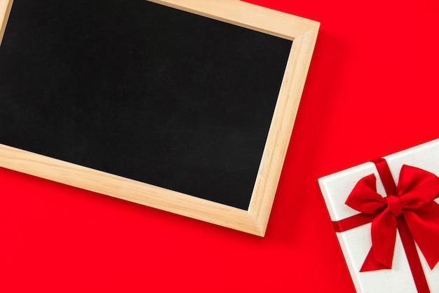 境界にギフトボックスと赤の背景に空の黒板