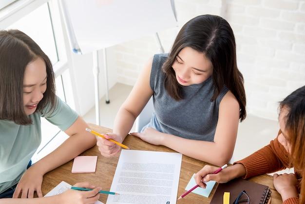 海外の大学生のアジアの女性学生がテーブルで課題をしている