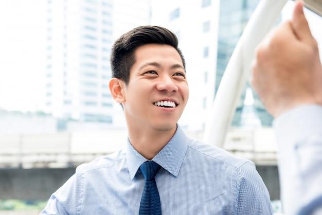 屋外の同僚と話す友好的なアジア人のビジネスマン