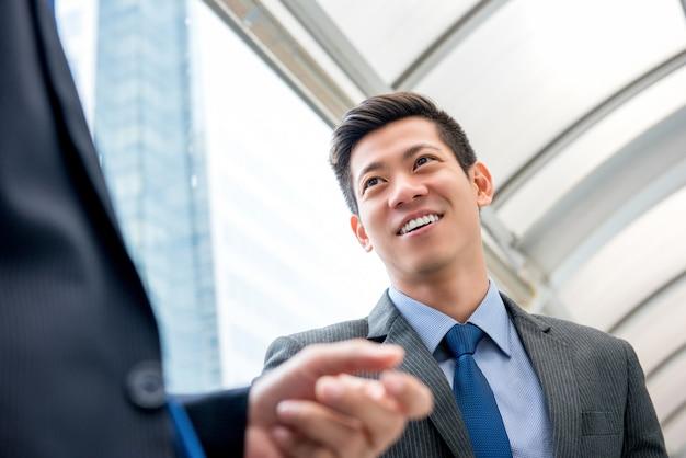 屋外でパートナーと話す若いハンサムなアジア人中国人のビジネスマン