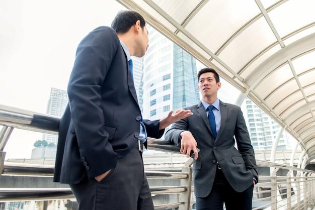 屋外で覆われた歩道で同僚と話しているアジアの中国人のビジネスマン