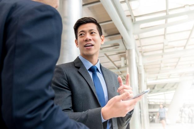 屋外で覆われた歩道で彼の同僚と話すアジア人のビジネスマン