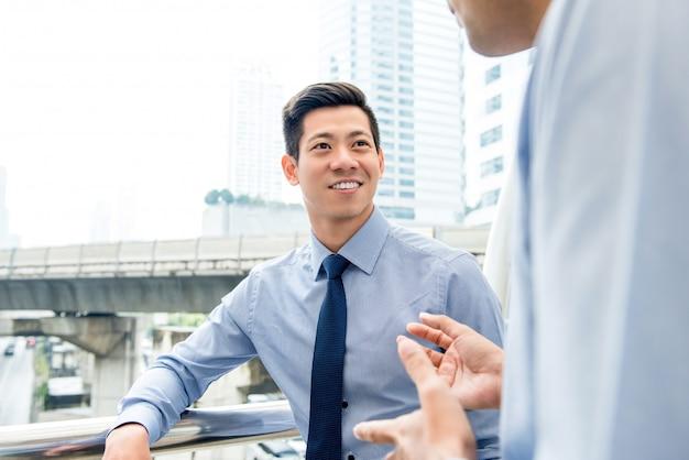 同僚の野外で話すハンサムなアジアの中国人のビジネスマン