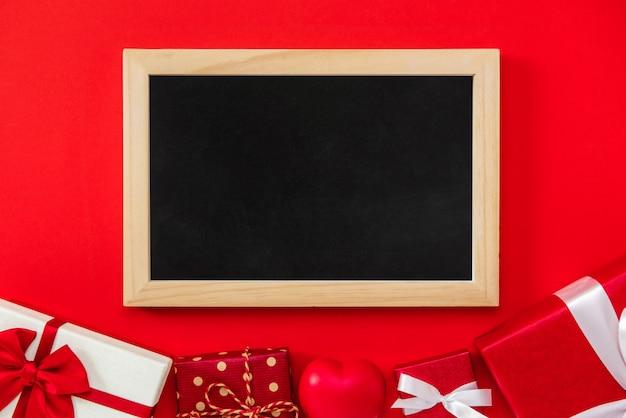 ボーダーのギフトボックスと赤い背景に空の黒板