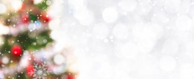 国境に雪とぼんやりとしたクリスマスツリーが装飾された抽象的な白いボケ