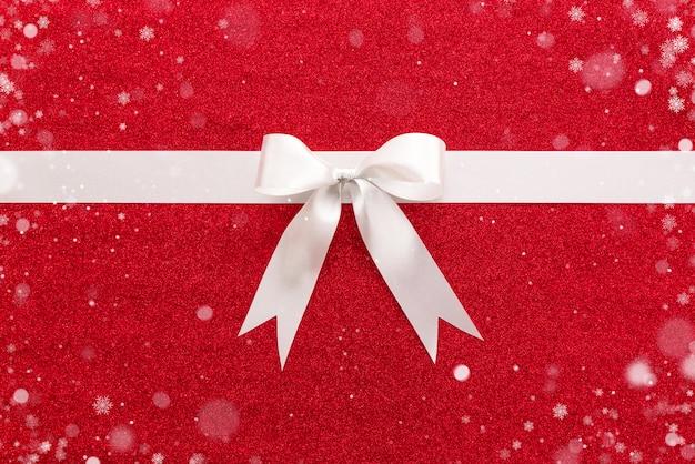 カラフルな赤い光沢のある紙の背景に弓と白いリボン