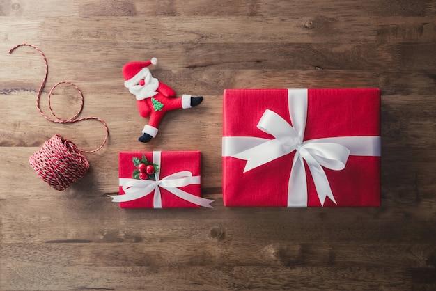 Красные новогодние подарочные коробки и предметы декора на фоне дерева