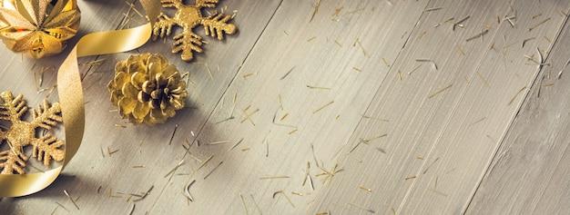 ゴールデンカーリーリボンと木のバナーの背景にキラキラクリスマスの装飾品