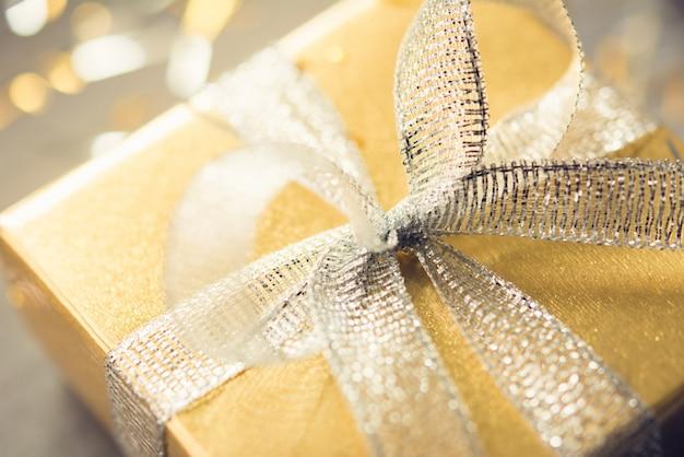 光沢のあるシルバーリボンの弓とゴールドラッピングペーパー付きギフトボックス