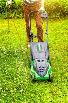 裏庭の芝刈り機で緑の草を刈る男。ガーデニングの国のライフスタイルの背景。